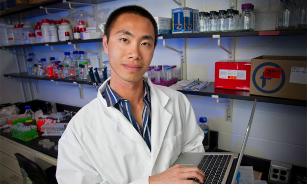 Desmond Lun in lab with computer.